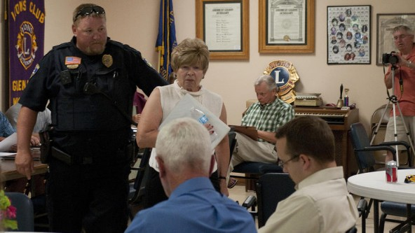 Photo credit New Richmond News. Resident Carol Vaga is escorted from meeting when she voiced concerns about mining when public comments were closed. Property owner Scott Teigen (blue shirt) looks on, Vista Sand's lawyer Anders Helquist (white shirt), city attorney from Bakke Norman (plaid shirt).